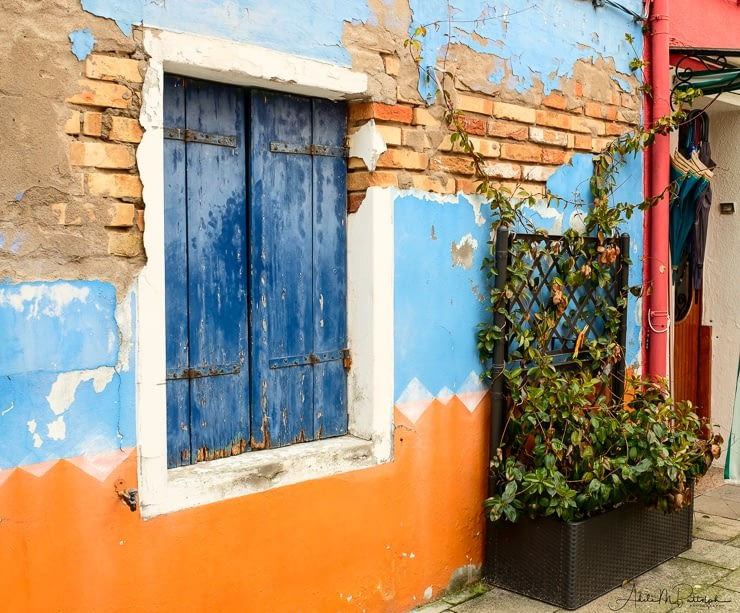 A blue, orange, and brick wall with a blue shutter in the window. Shot in Burano, Italy.