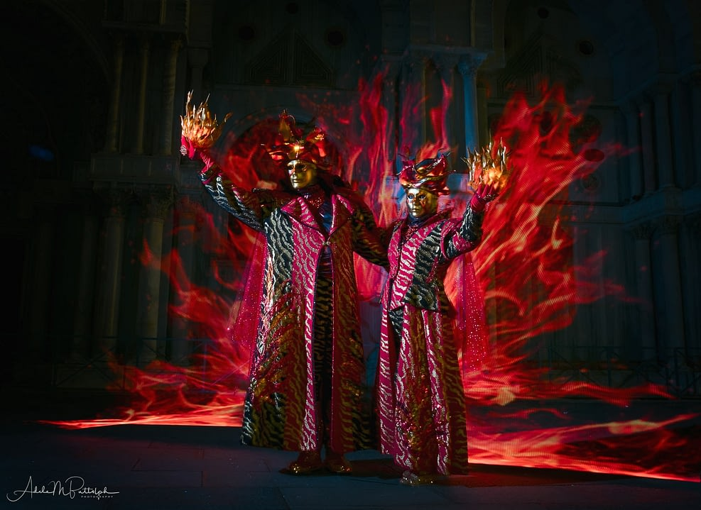 Venice Carnival 2018 in flame costumes with fire and flames behind them. Flame people.