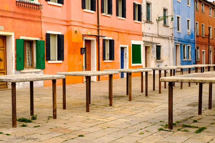 Market tables and colorful buildings, Burano, Italy