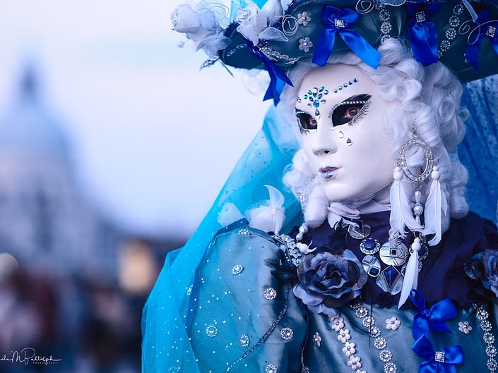 Portrait of a blue and white costumer photographed at Venice Carnival 2018.