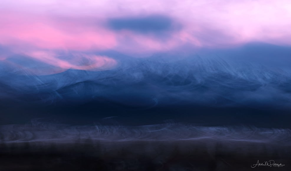 Pink and blue colors of a winter dusk swirl over and in front of Ruby Peak, Wallowa Mountains, Oregon