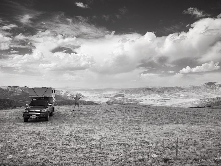 Photograph of man and camper parked at a spot in the Gravelly Range, Montant that overlooks adjacent mountains. Image was shot in infrared and converted to black and white.