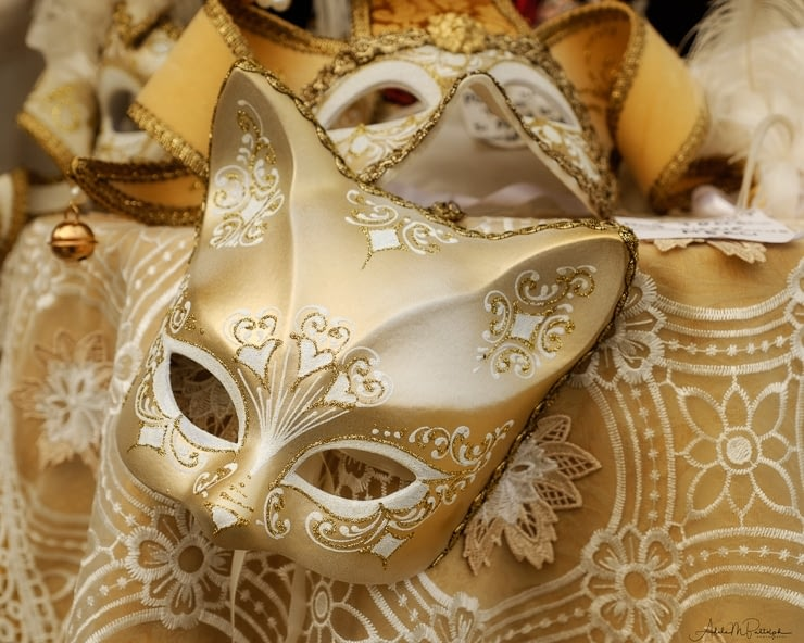A golden cat mask is showcased on a table of Carnival masks in Burano, Italy.