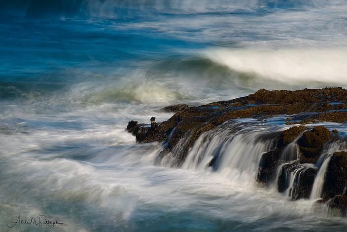 Water flows off of coastal rocks amid a churning ocean at Cape Perpetua, Oregon
