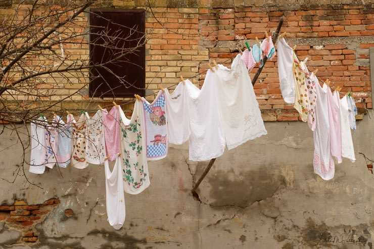 A clothesline full of laundry is held up by a stick in a concrete wall in Burano, Italy.