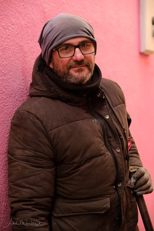 Portrait of a municipal worker standing against a pink wall, Burano, Italy