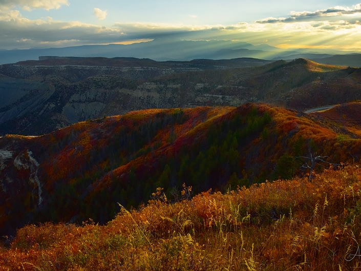 Early morning sunbeams illuminate autumn color on ridges at Mesa Verde National Park, Colorado.