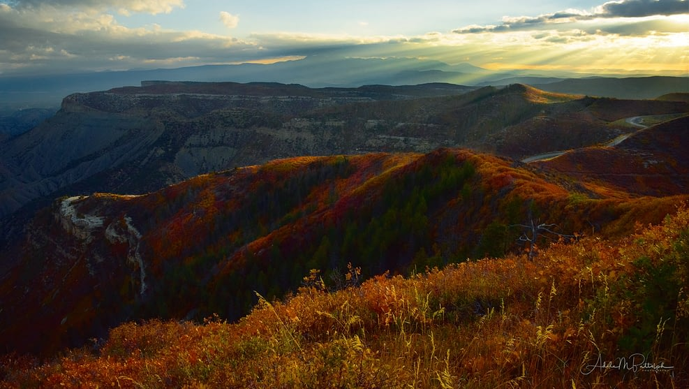 Early morning sunbeams illuminate autumn color on ridges at Mesa Verde National Park, Colorado.