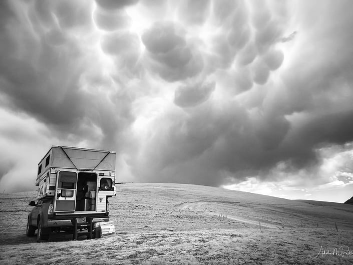 Black and white infrared photograph of a storm brewing over a camper in the Gravelly Range, Montana.