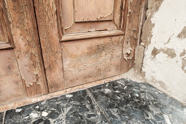 Bottom of the entryway to a building showing peeling paint, terrazo landing, and worn wall. Photographed in Burano, Italy.