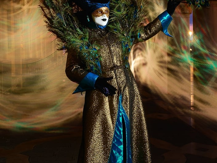 Peacock themed costumer poses on St. Mark's Square under the portico during Venice Carnival. A Pixelstick was used to create swirled light behind her.