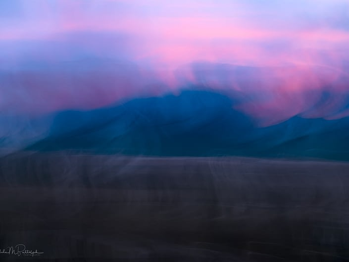 Dynamic pink and blue clouds captured with camera motion dance on the Wallowa Mountains, Oregon.